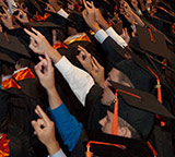 students at graduation flashing hookem horns sign